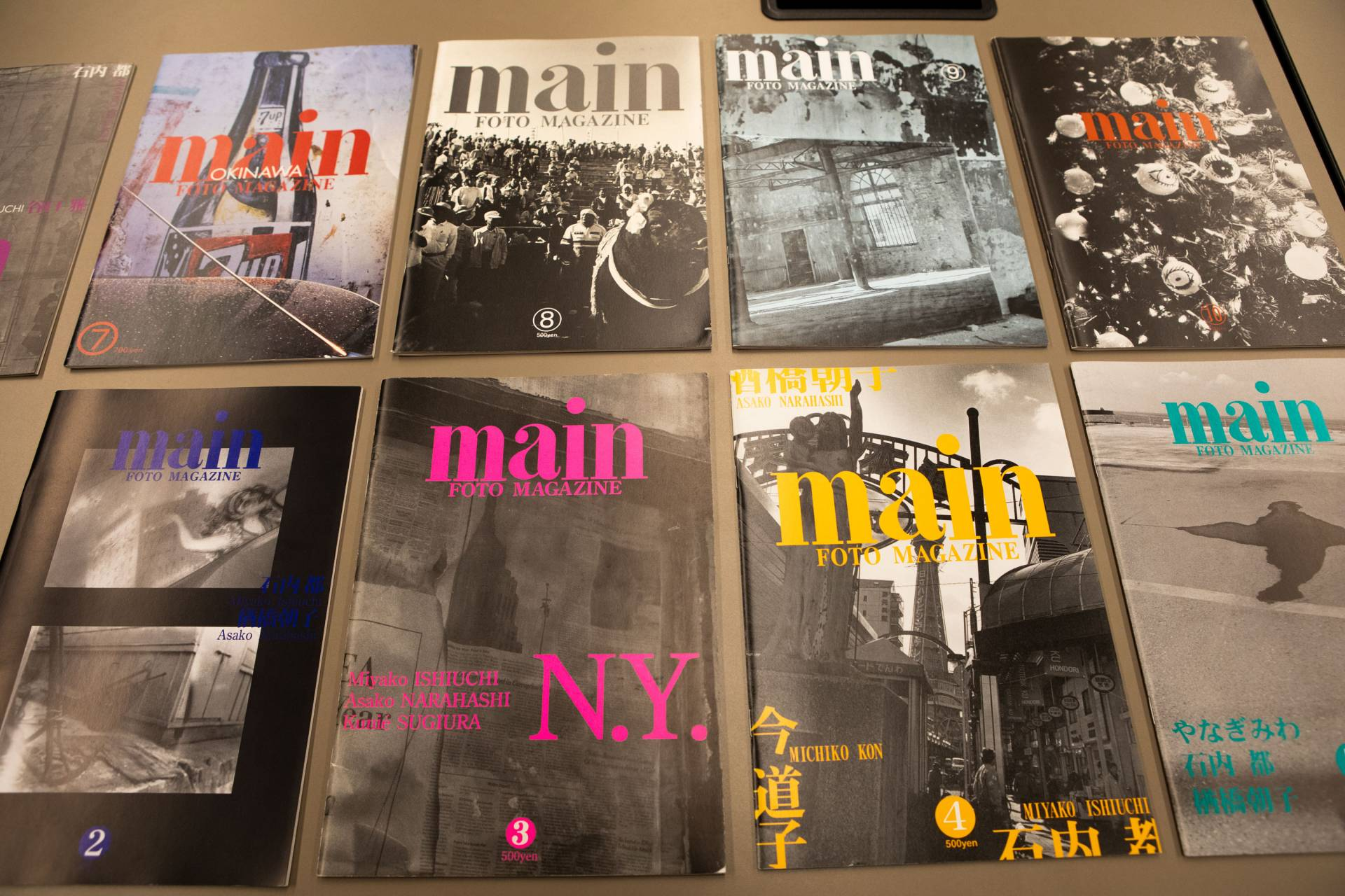 "Issues of ""Main"" laid out on a table in a grid"