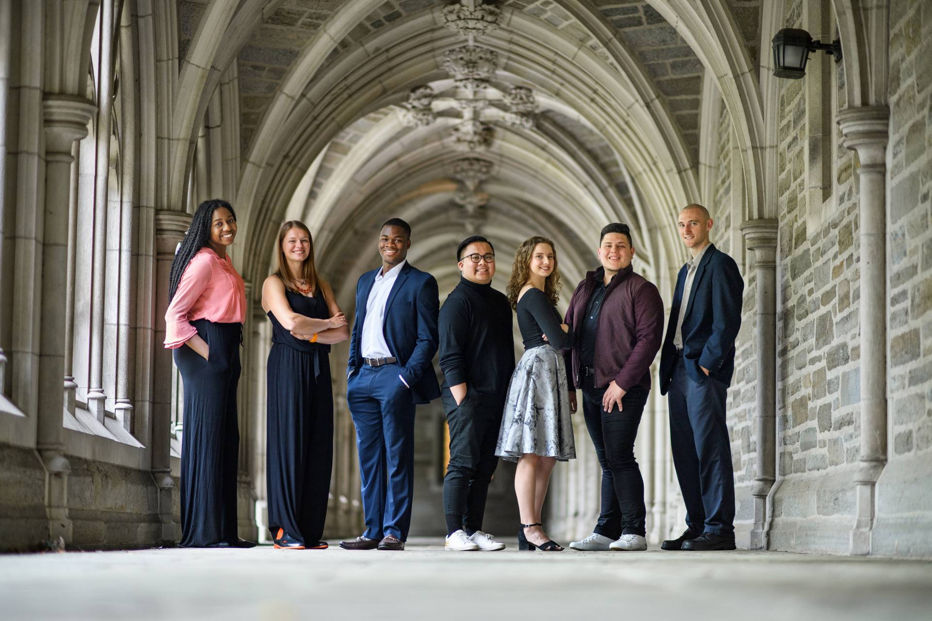 Nenna Ibe, Hannah Paynter, Moyin Opeyemi, G.J. Sevillano, Marcia Brown, Samuel Vilchez Santiago and Kyle Lang standing in an iconic archway