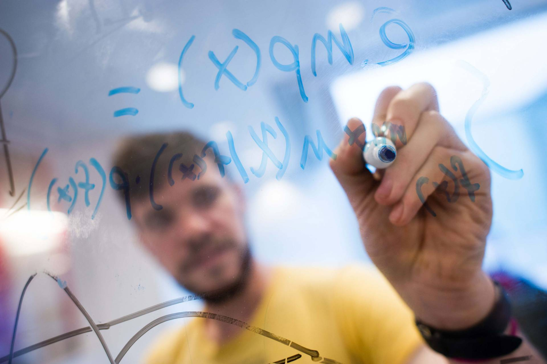 A student writes math formulas on a plexiglas surface