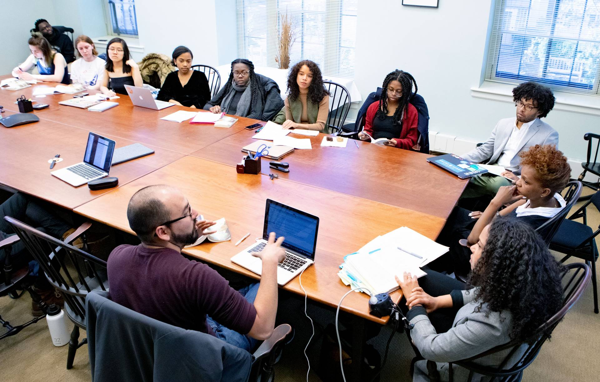 Students sit at a table discussing the works of Toni Morrison