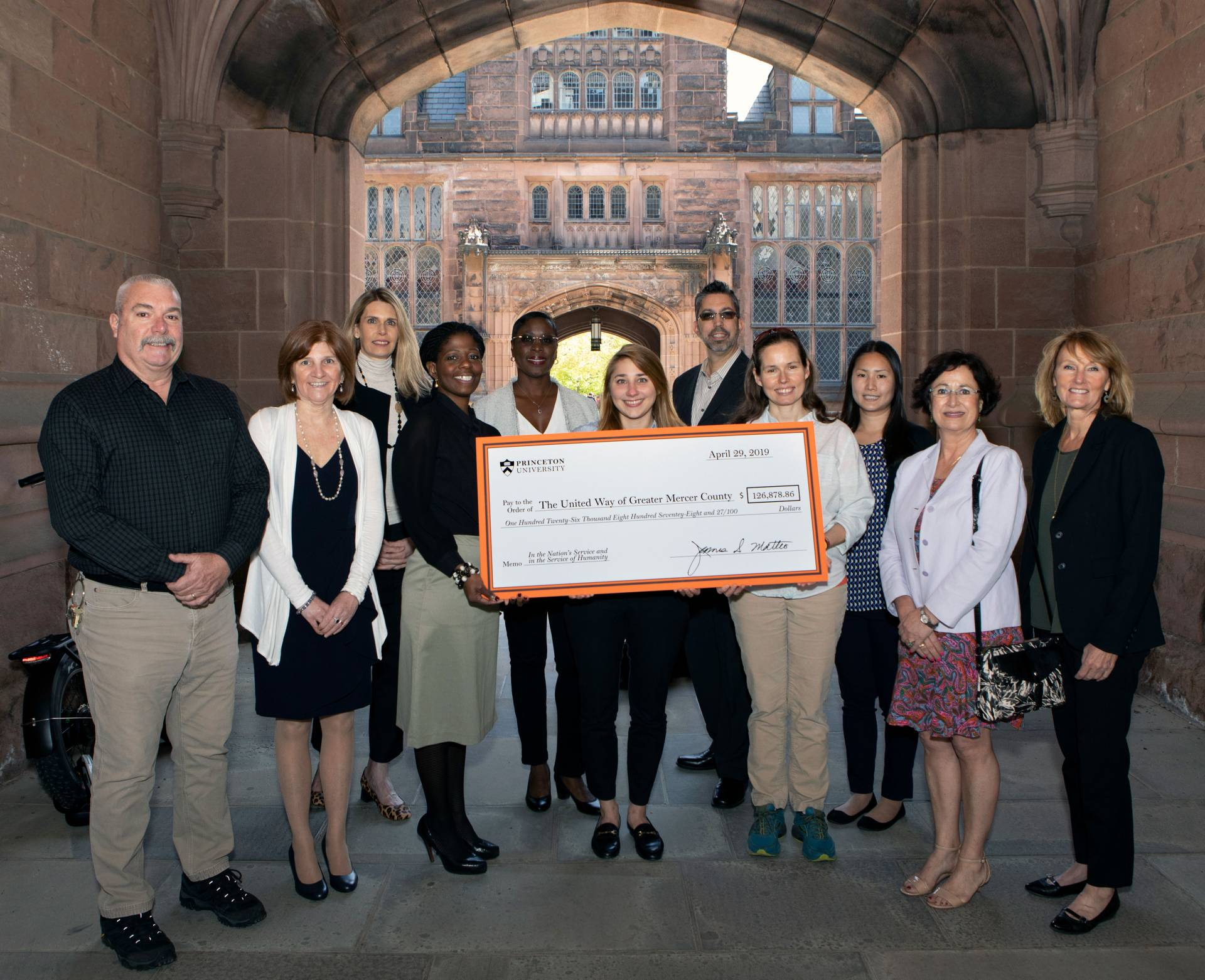 Staff members pose with a giant check from Princeton to the United Way