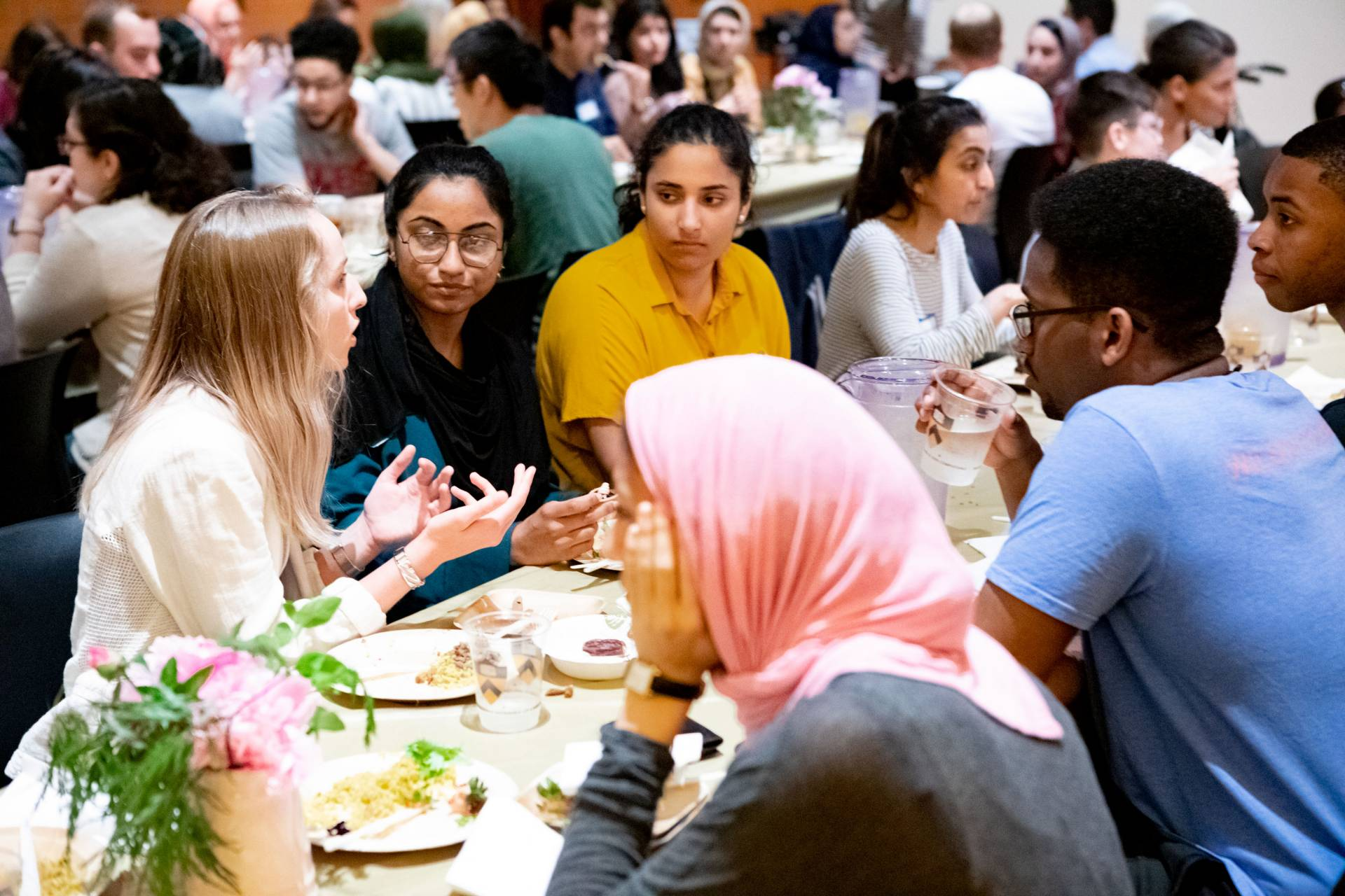 Students eating and speaking with one another at the interfaith dinner