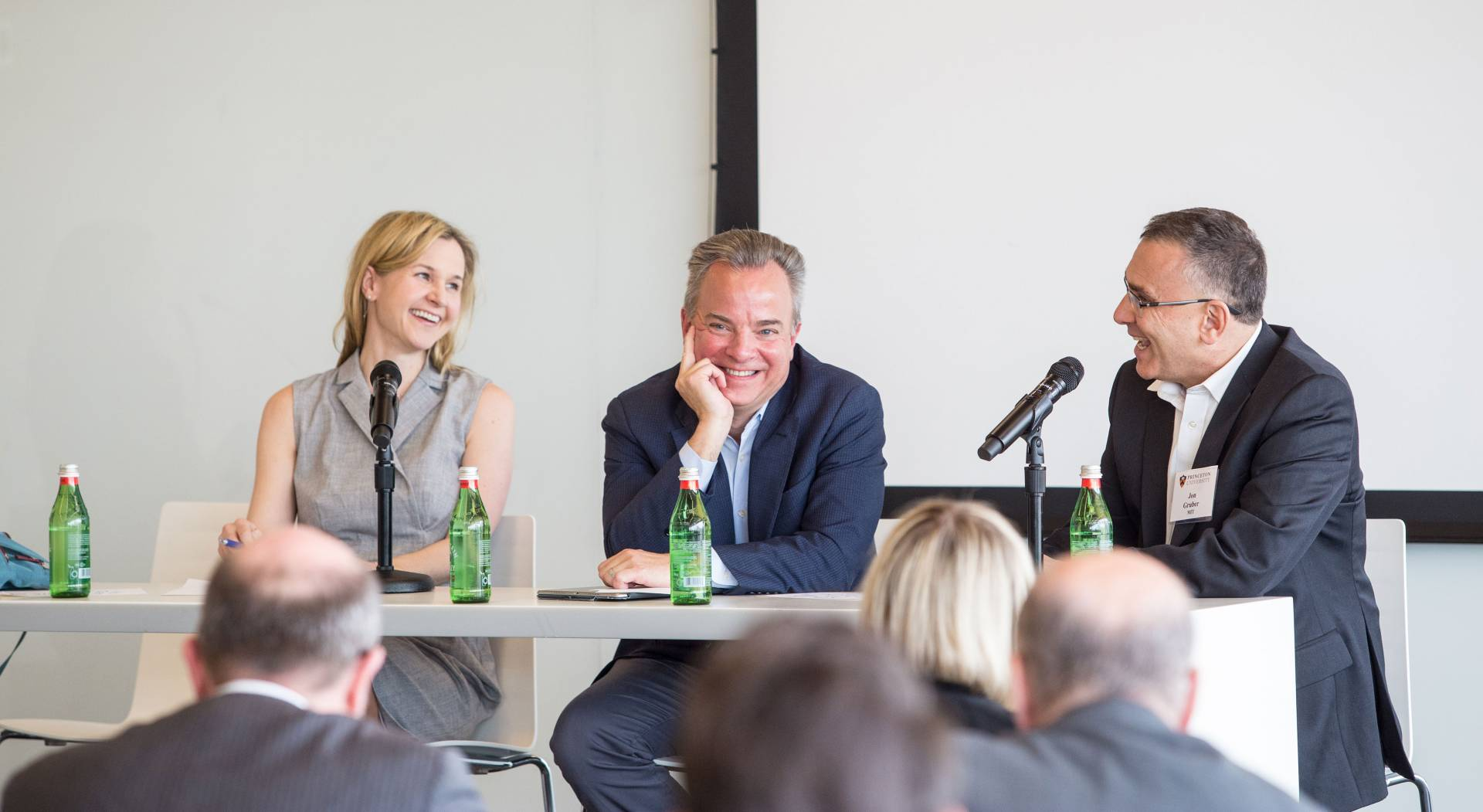 Three experts speak on a panel in front of an audience