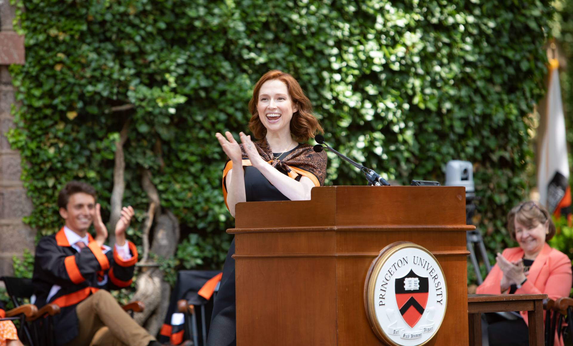 Ellie Kemper claps and laughs at the podium