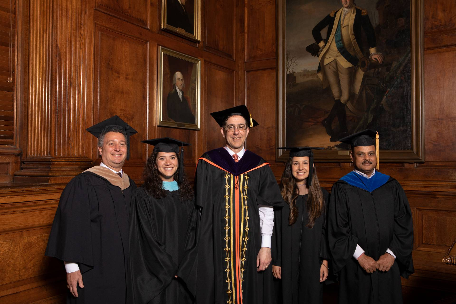 Kevin Killian, Kimberly Dickstein, Petrina Plunkett and Dr. Arun Srivastava pose with Christopher L. Eisgruber in ceremonial black gowns and mortarboards
