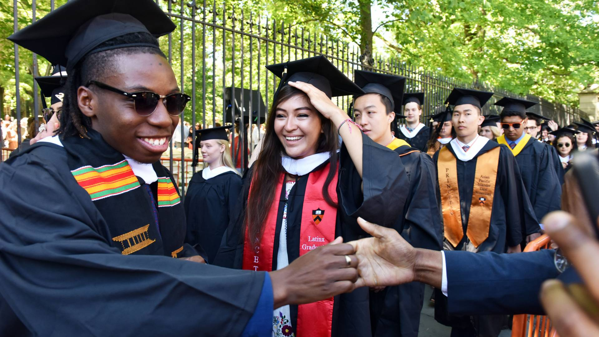 Student shaking hands with onlooker while processing toward campus for Commencement