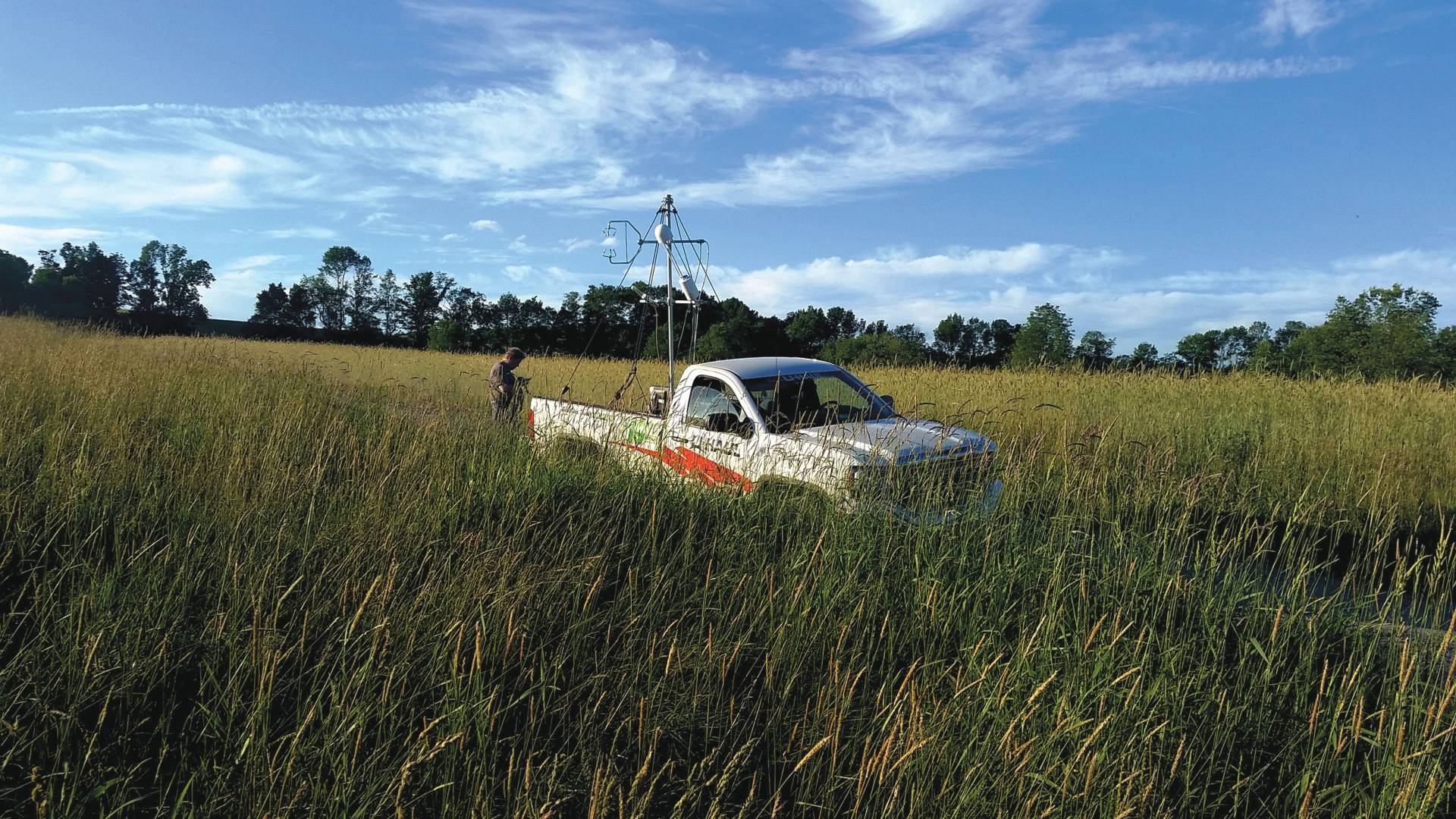A researcher in a field beside a mobile lab