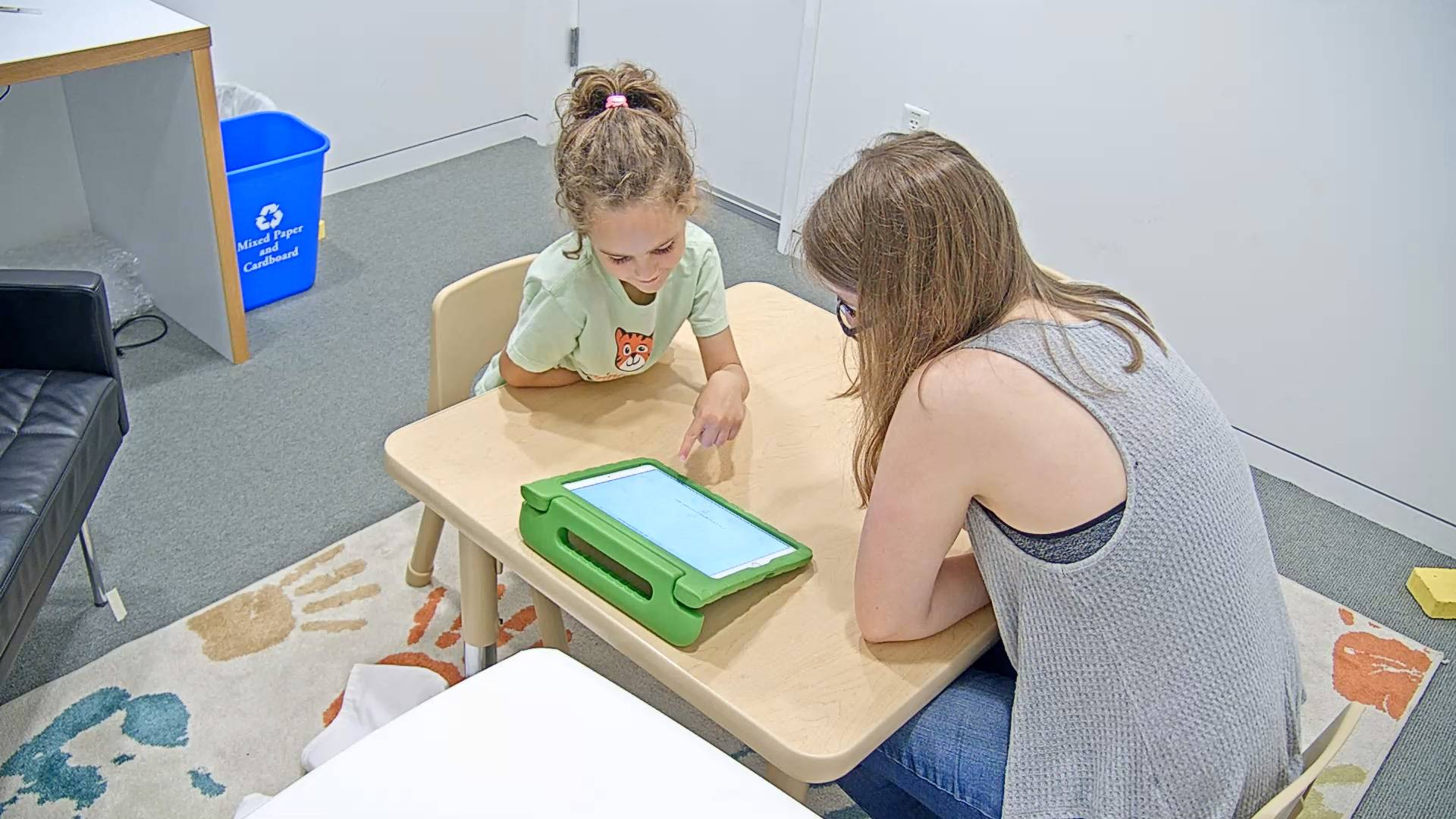 A child looks at a screen with a researcher