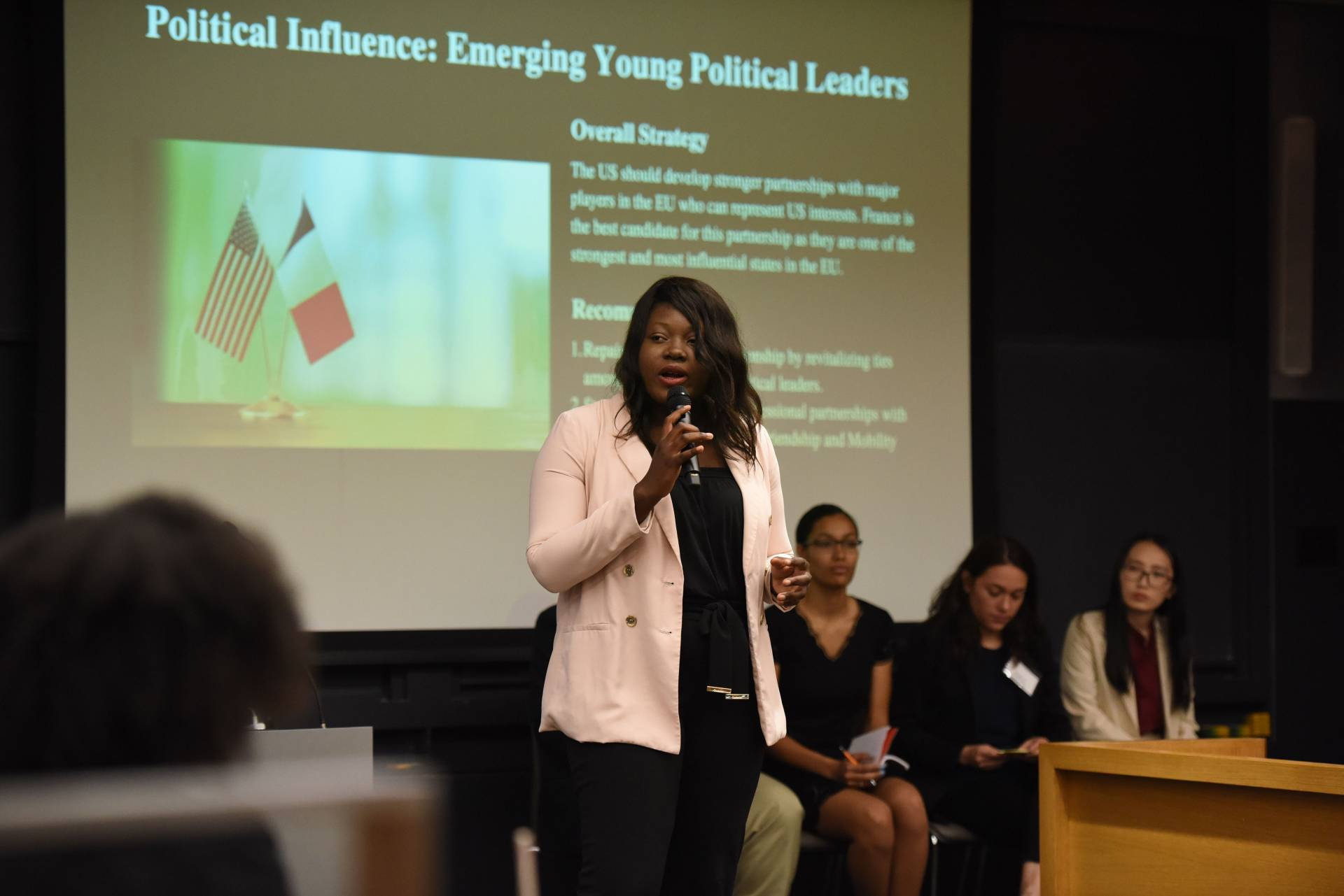 "A woman speaks to an auditorium-style classroom full of undergraduates in front of a projection that reads: ""Political Influence: Emerging Young Political Leaders"""