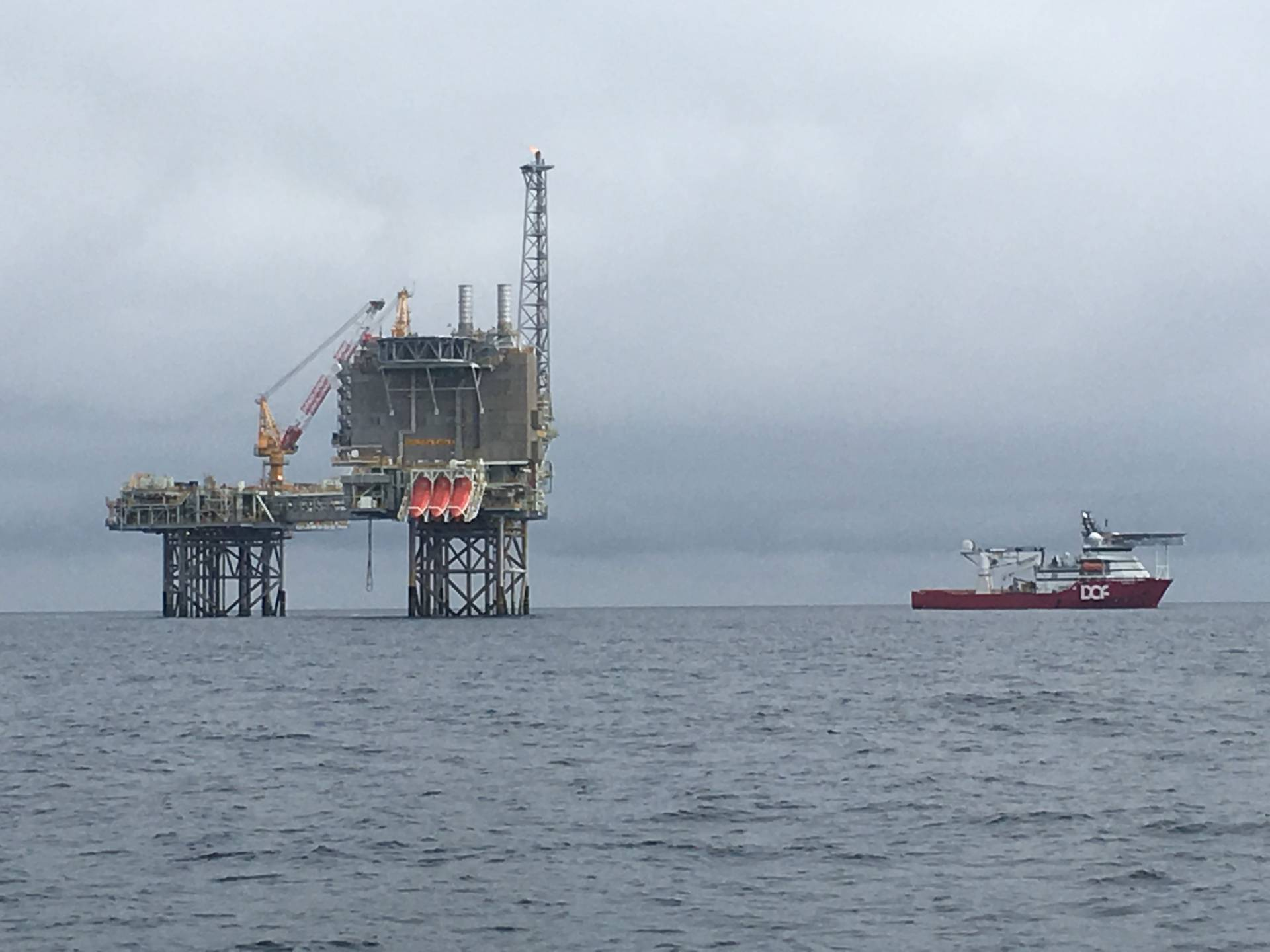 a boat and offshore oil drilling rig