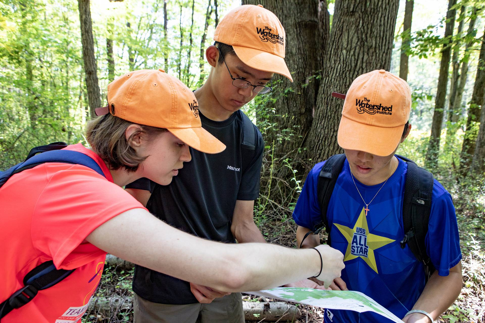 3 students look at a trail map