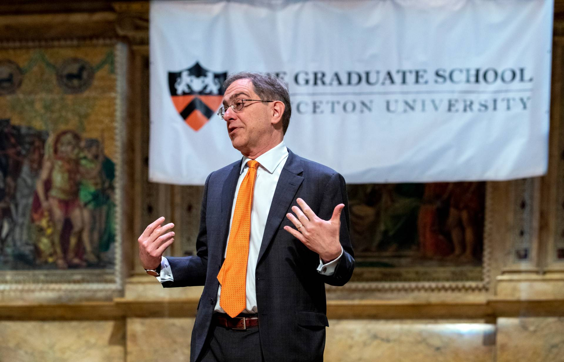 Christopher Eisgruber standing speaking in front of the Graduate School banner