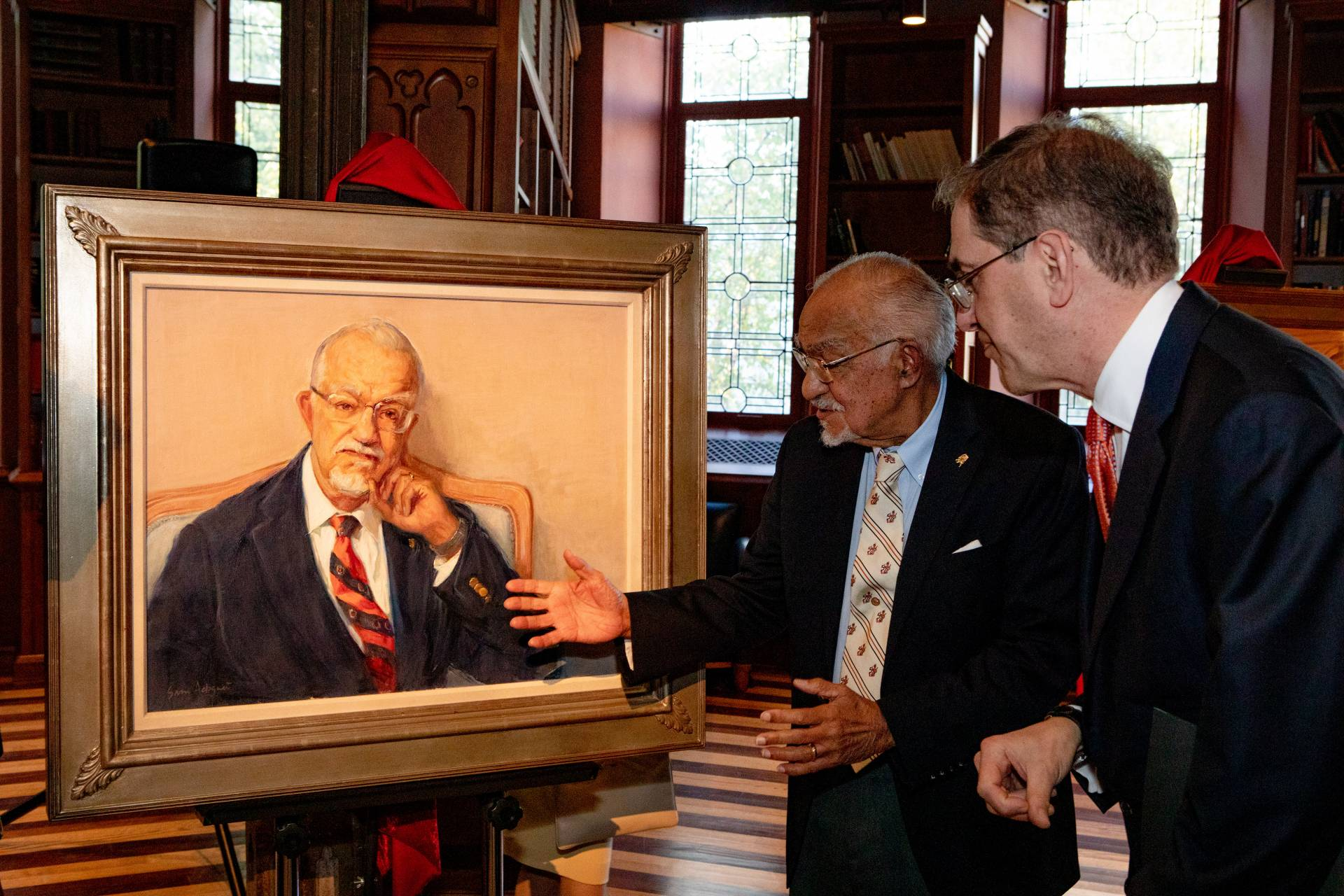Rivers looks at his portrait with the president of the university