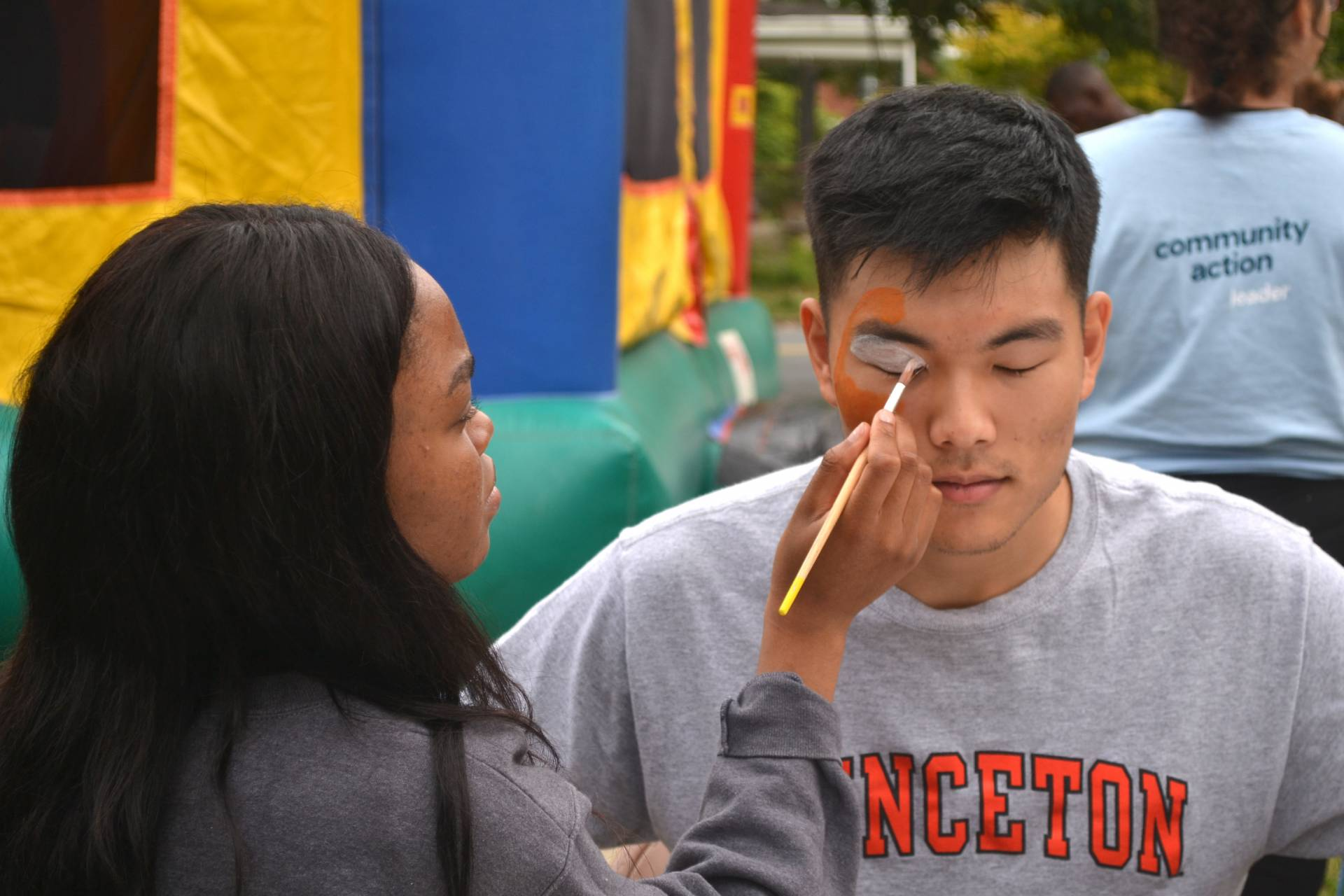 A student applies face paint on another student