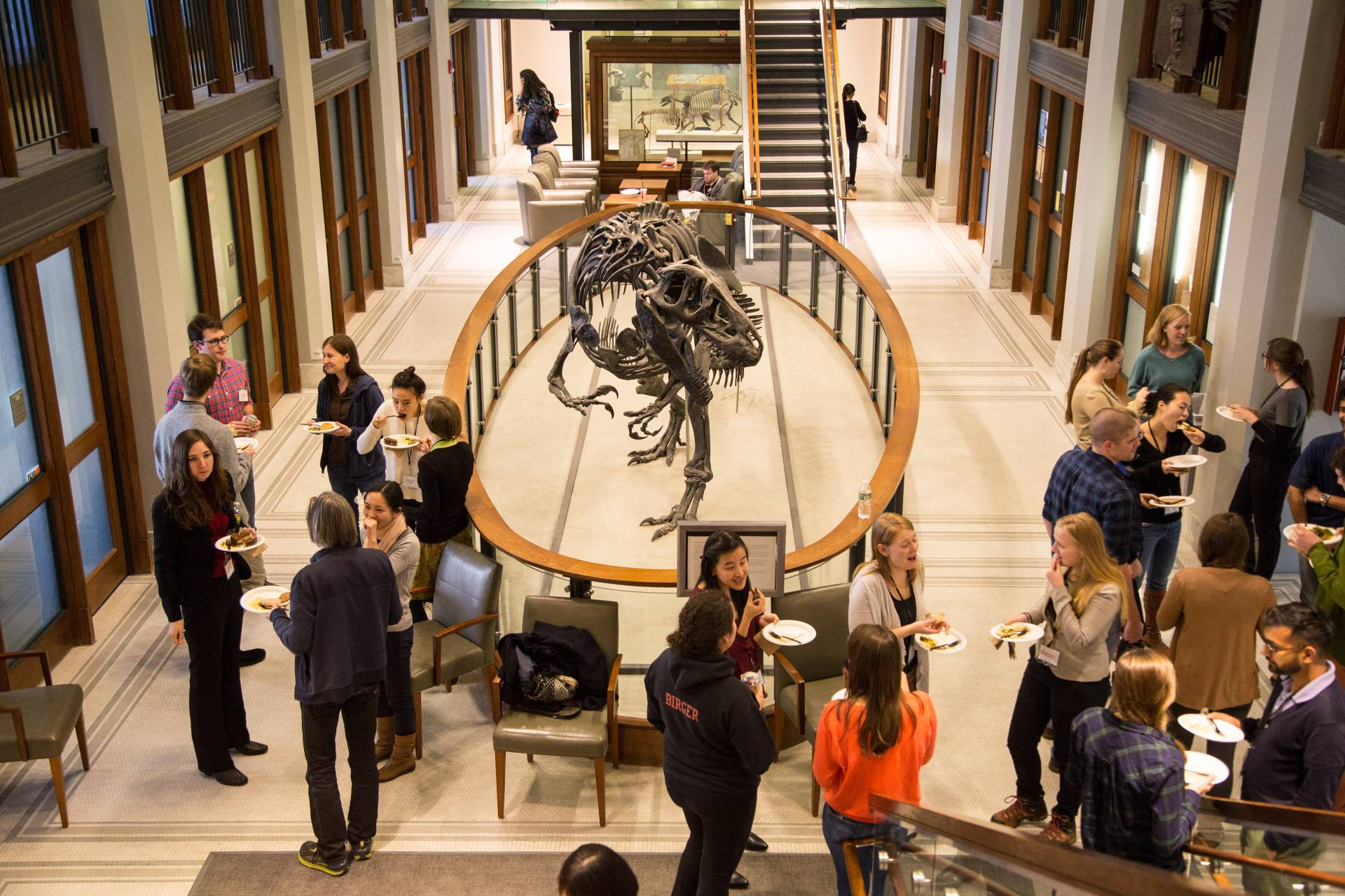 People at an event in the Guyot Hall atrium, in front of the dinosaur skeleton