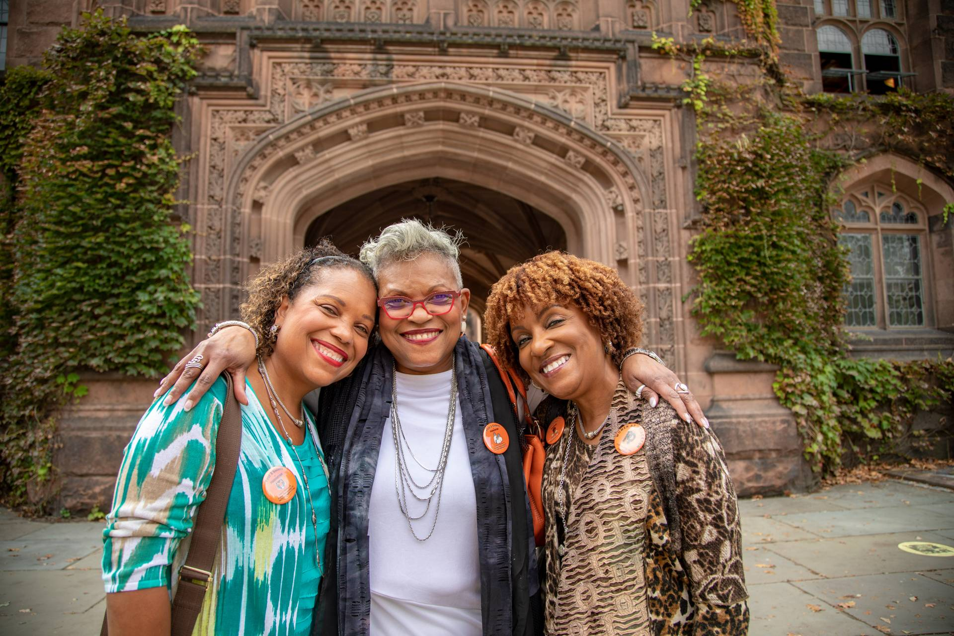 Three women stand and smiling on campus