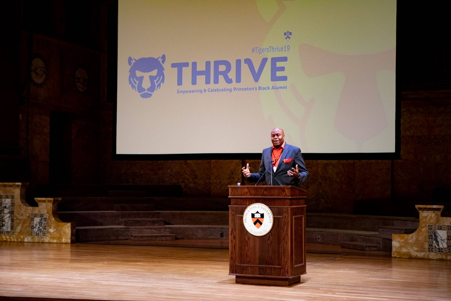 Craig Robinson speaking at podium in front of screen with the word THRIVE on it