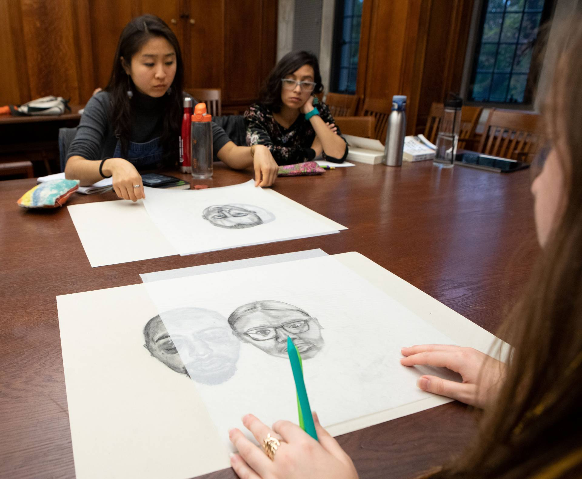 Students look at drawings of faces