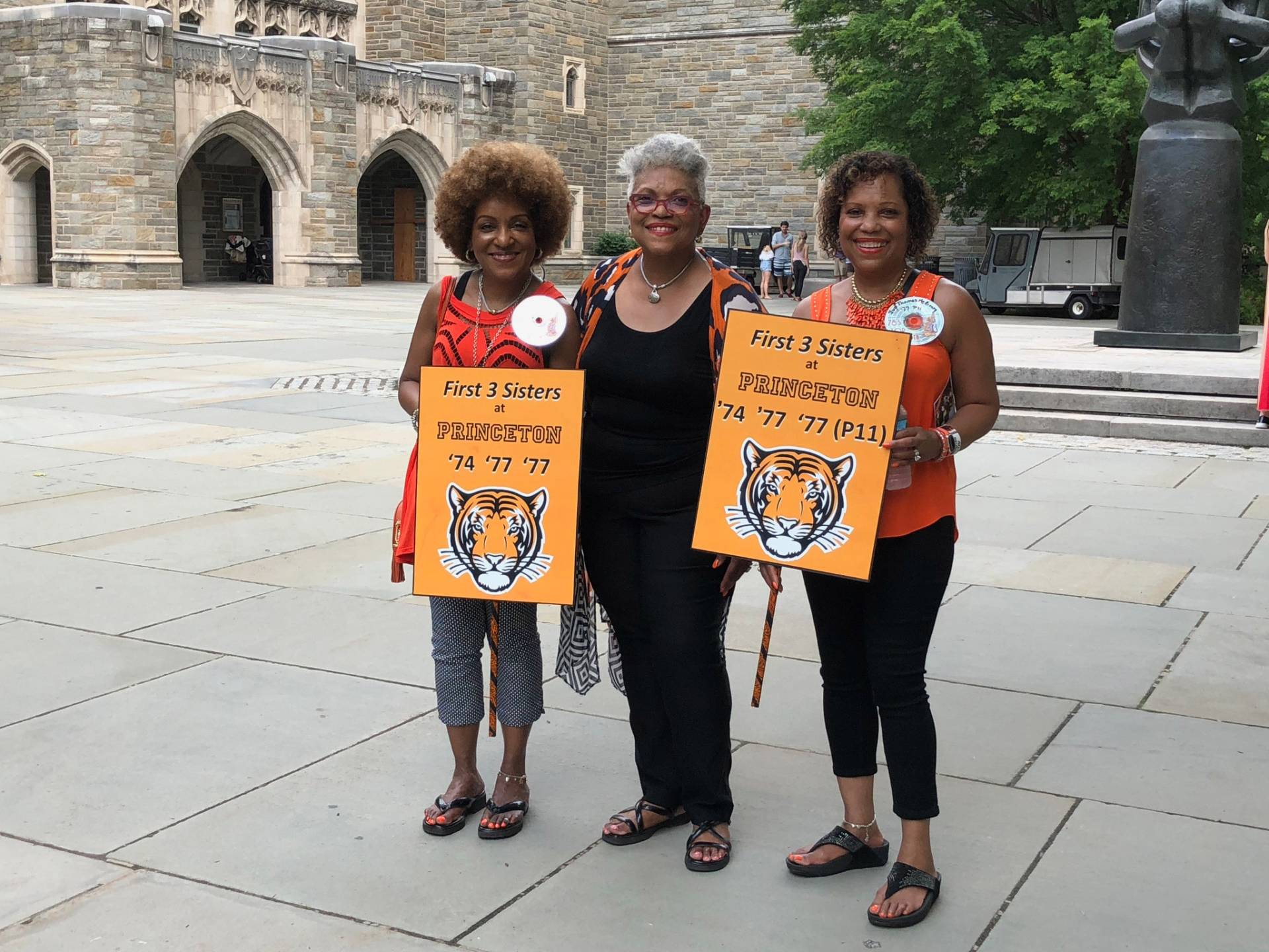 "Daphne, Evora, and Ivy at Reunions 2018, holding signs that read: "" First 3 sisters at Princeton '74, '77, '77"