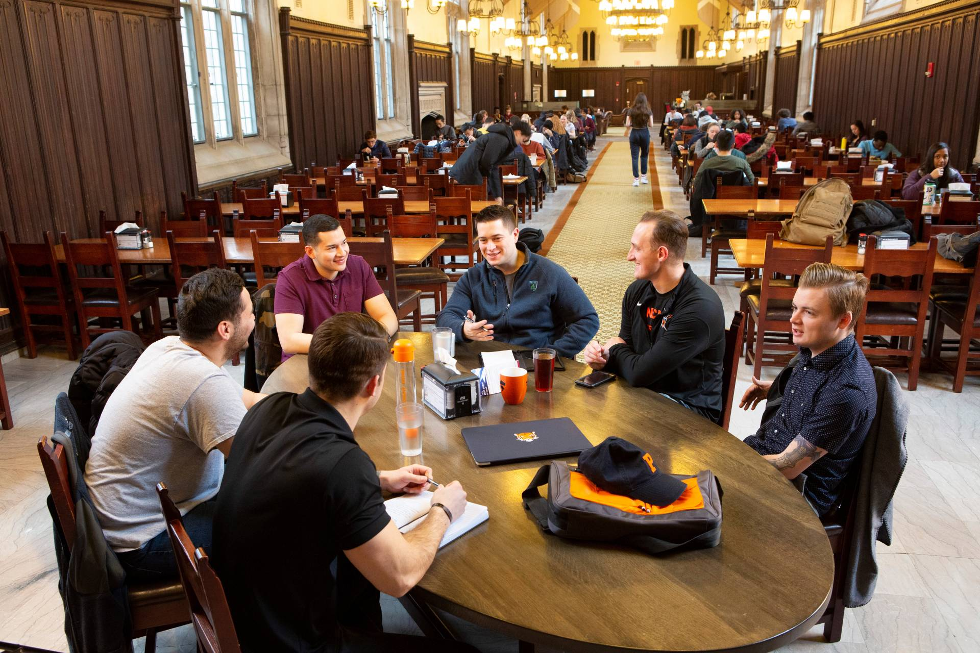 Students sitting around a table in a dining hall
