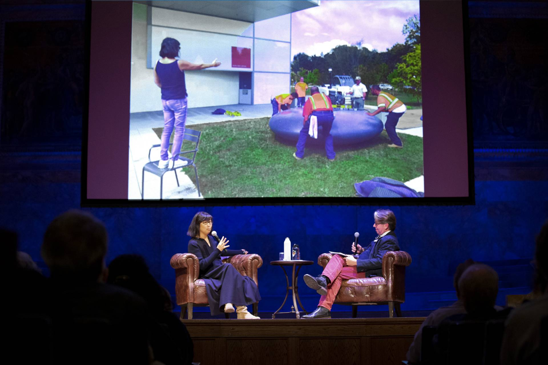 Maya Lin speaks with James Steward on stage about her installation and projects on a screen an image of her directing her colleagues positioning a large grey inner tube on a grassy square