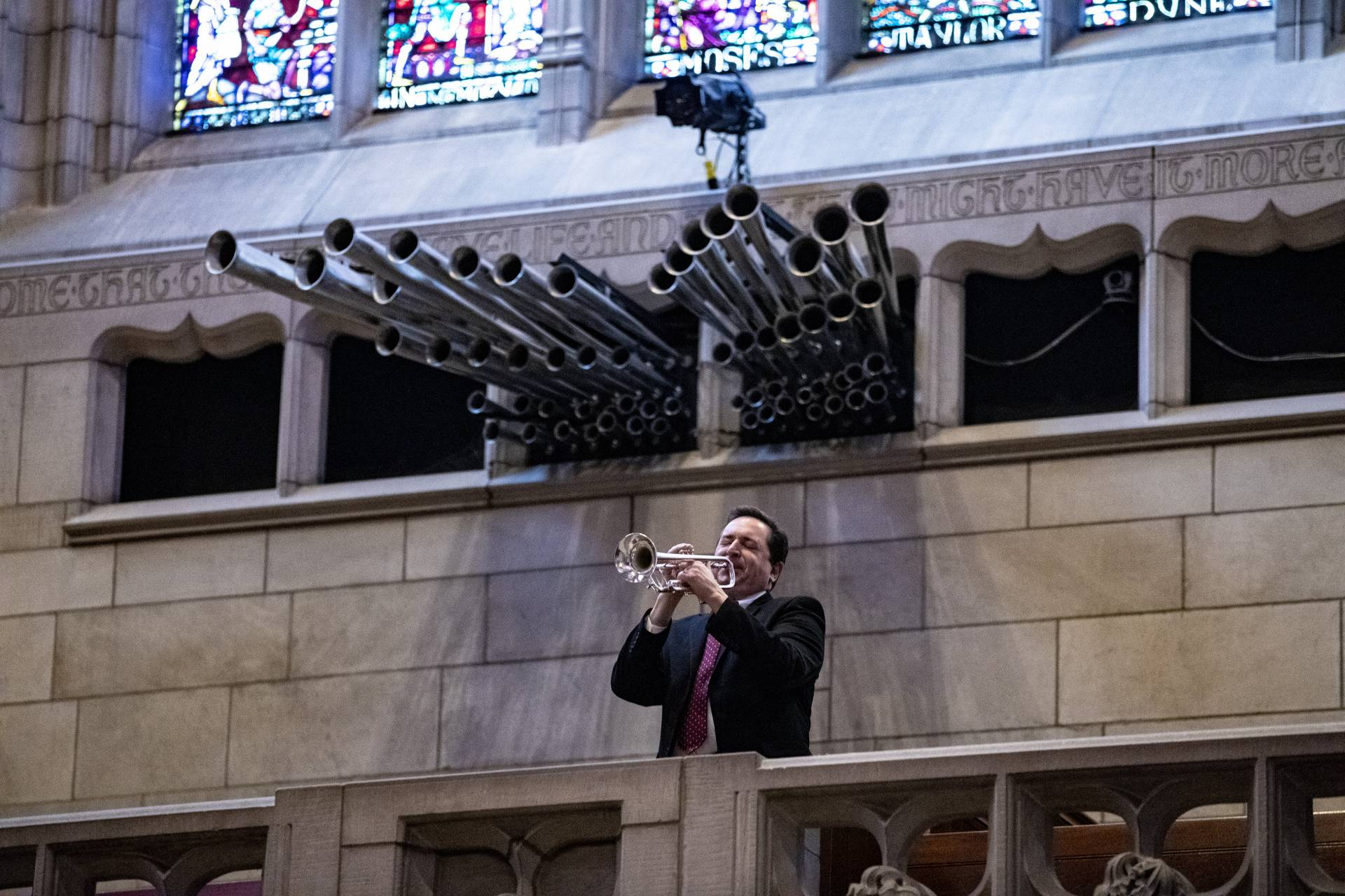 A man plays the trumpet underneath the pipes of the church organ