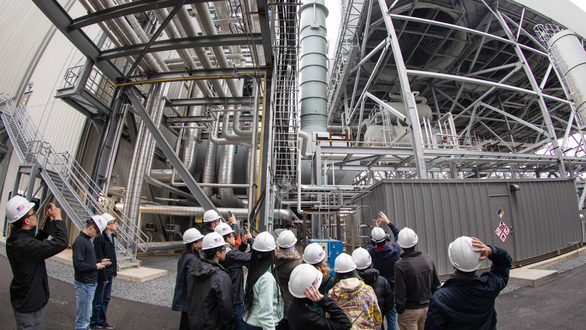 students in hard hats look at part of a power plant