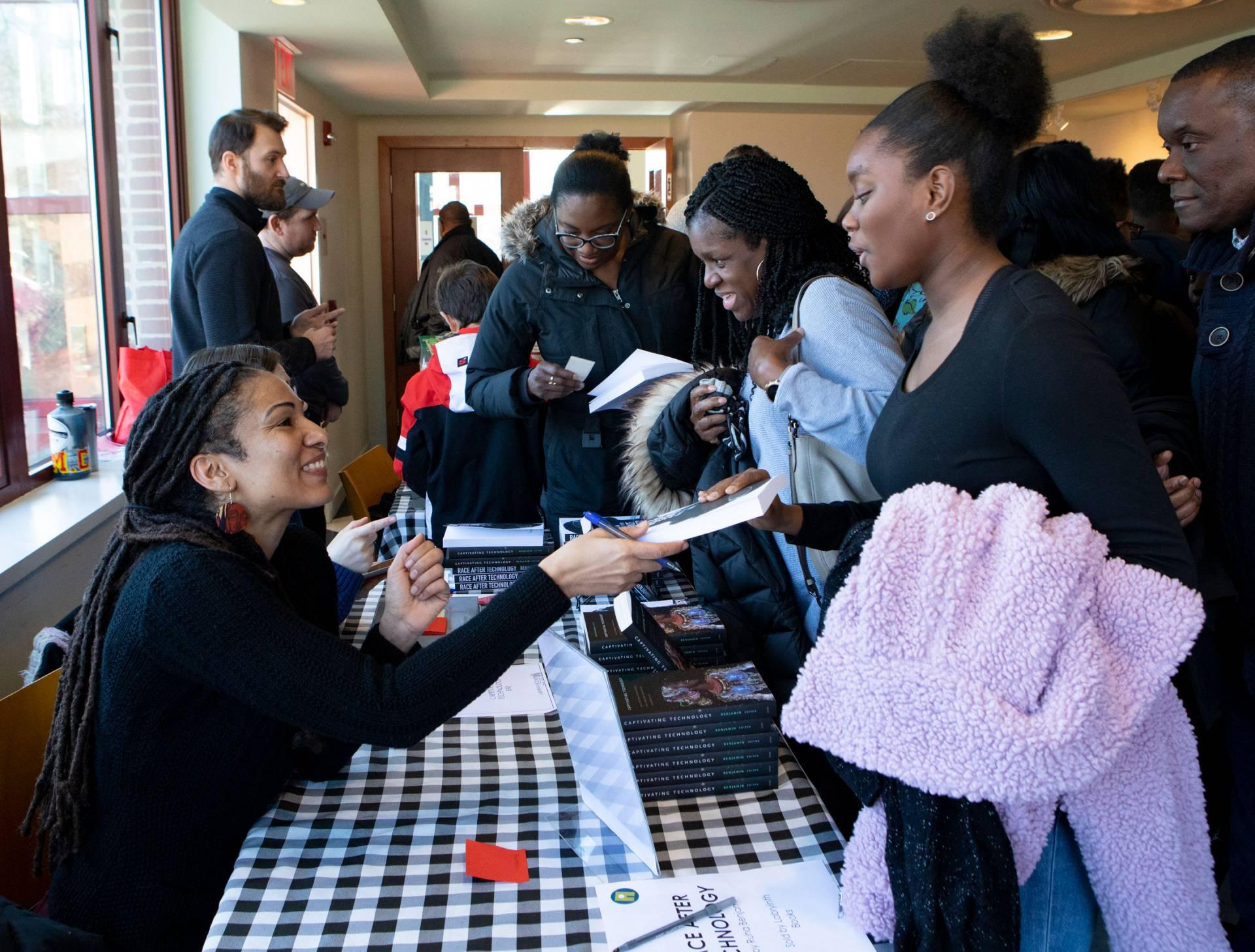 Ruha Benjamin signing books for community members