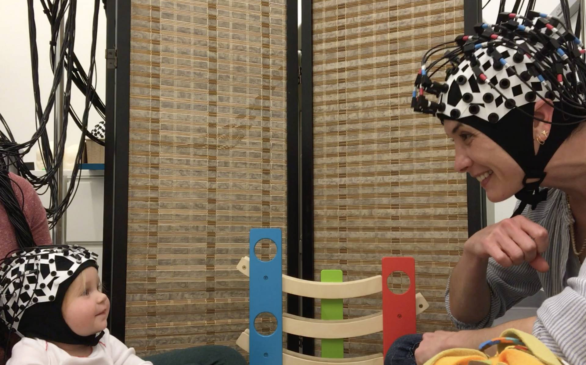 A baby and a researcher wear brain wavelength-measuring devises on their heads while making eyecontact during play
