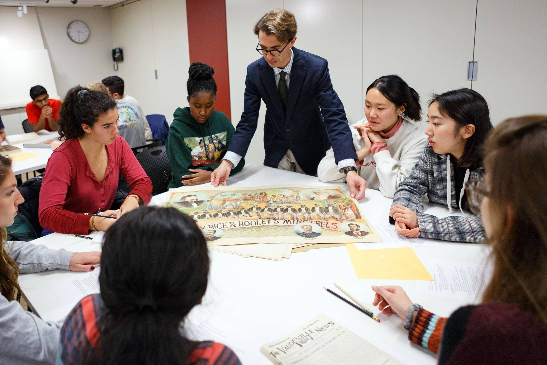 Professor and students look at materials from special collections