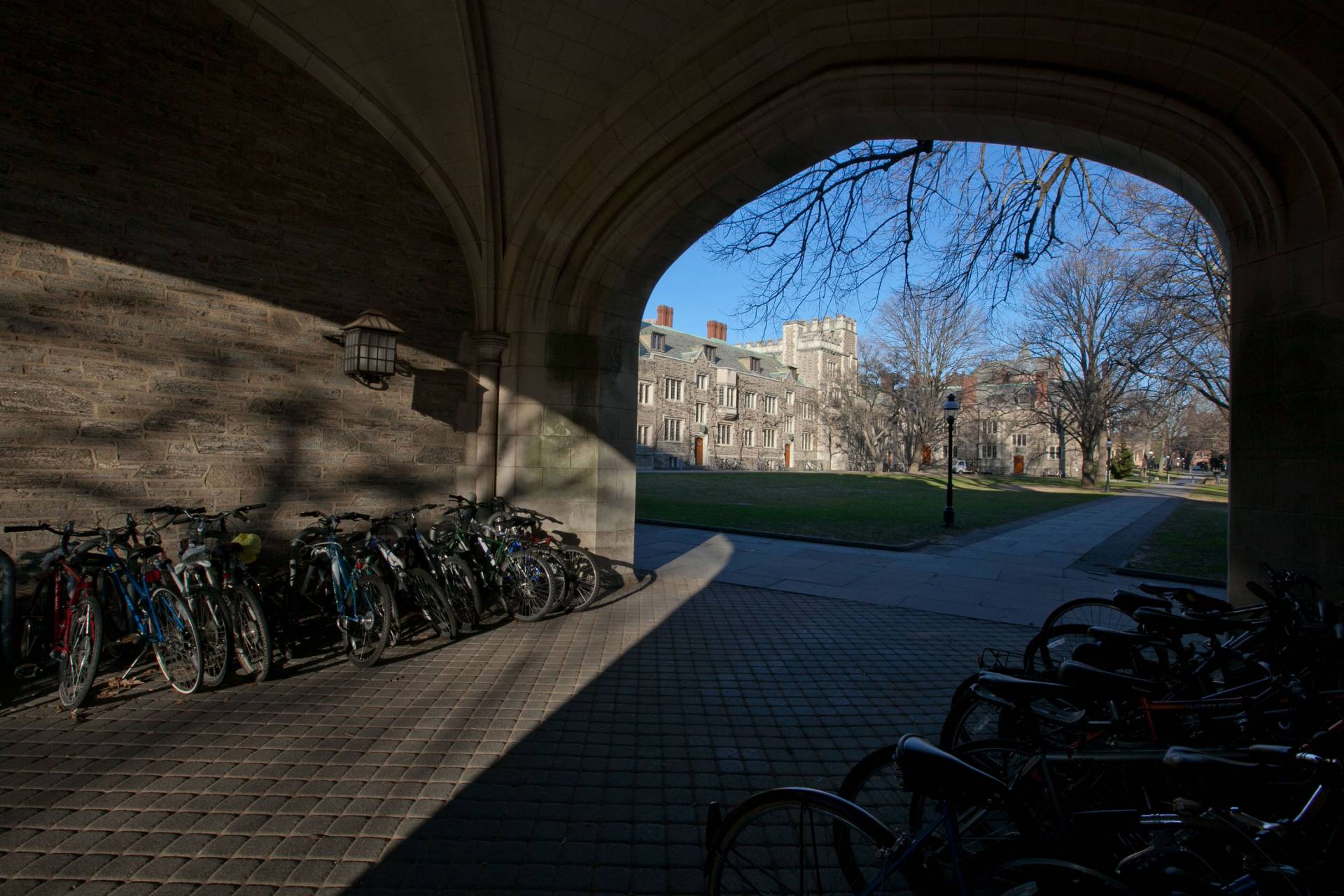 Sunlight falls on bicycles in an archway