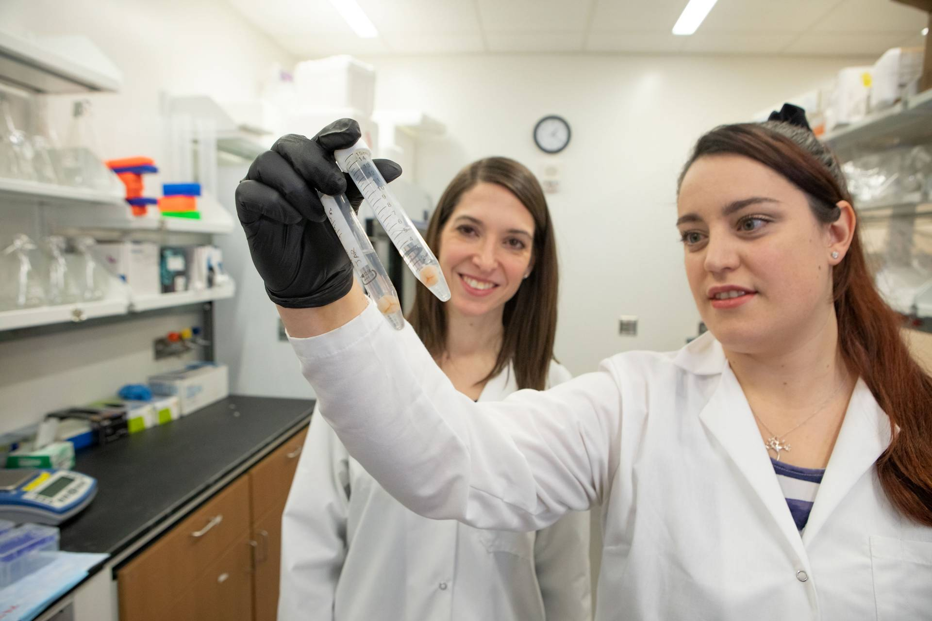 Two women in lab coats look at a test tube