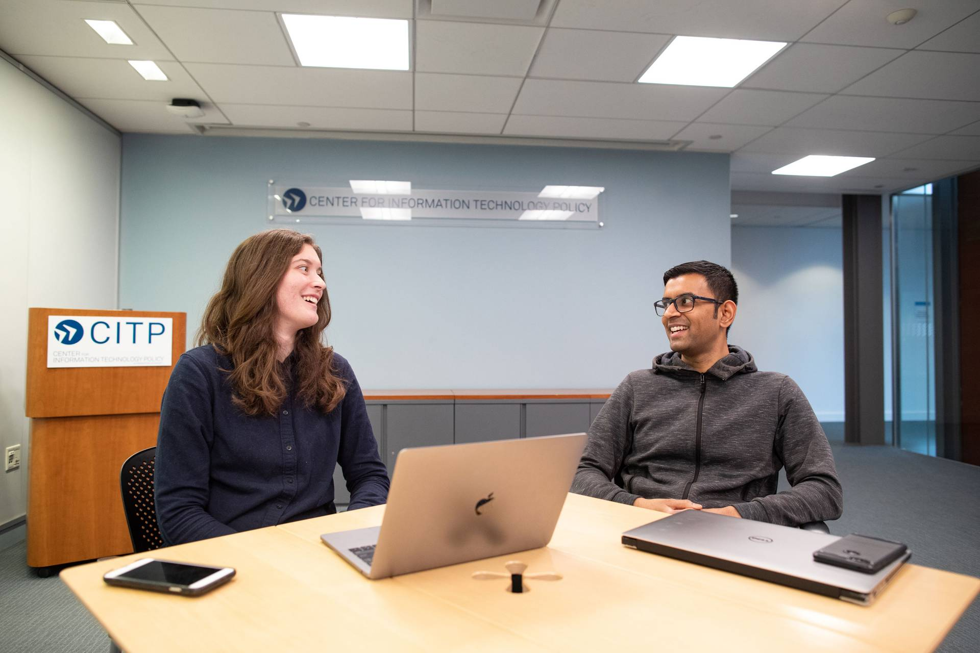 A graduate student and a professor speak over a laptop