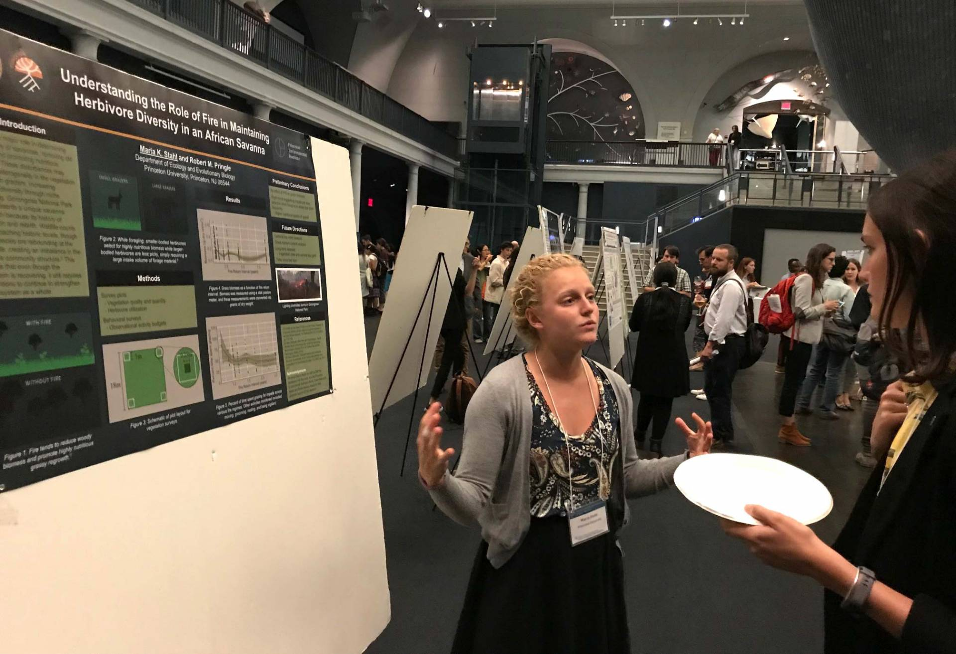 Stahl presents her research in front of her poster