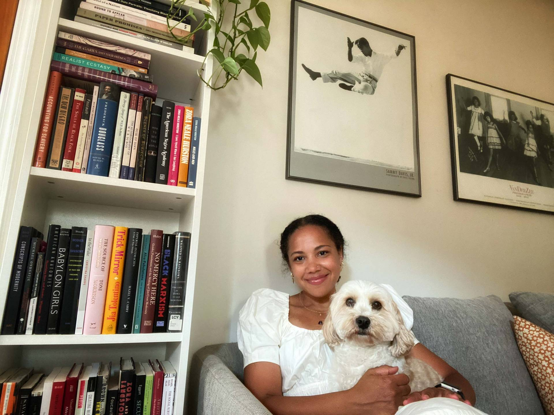 Autumn Womack with her dog next to bookshelves