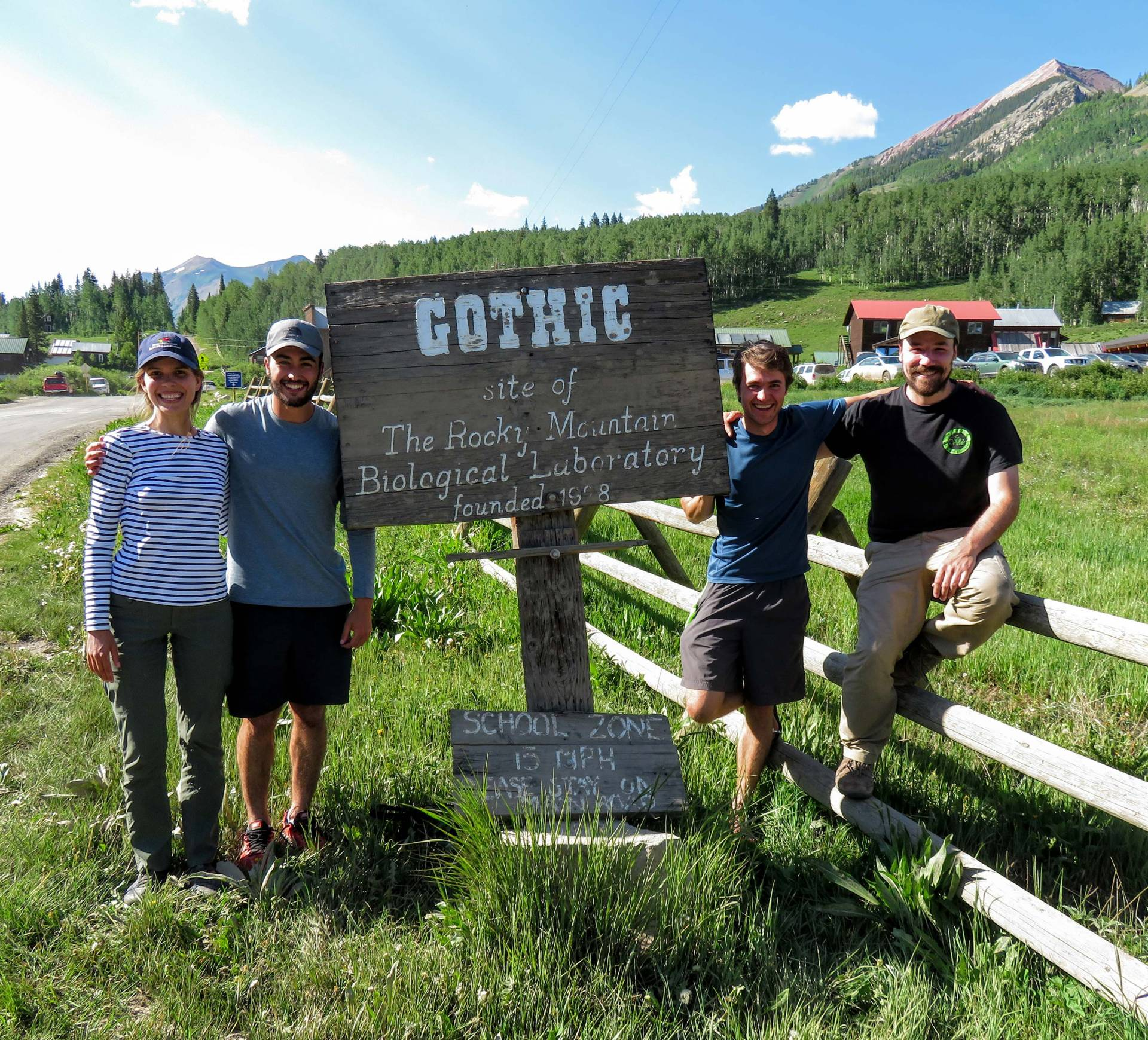 four researchers stand next to a sign at Rocky Mountain Biological Laboratory