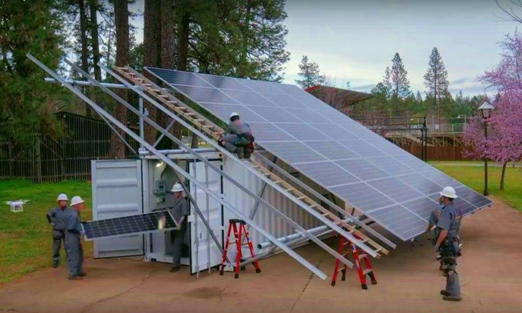 Workers set up a microgrid, complete with solar panels