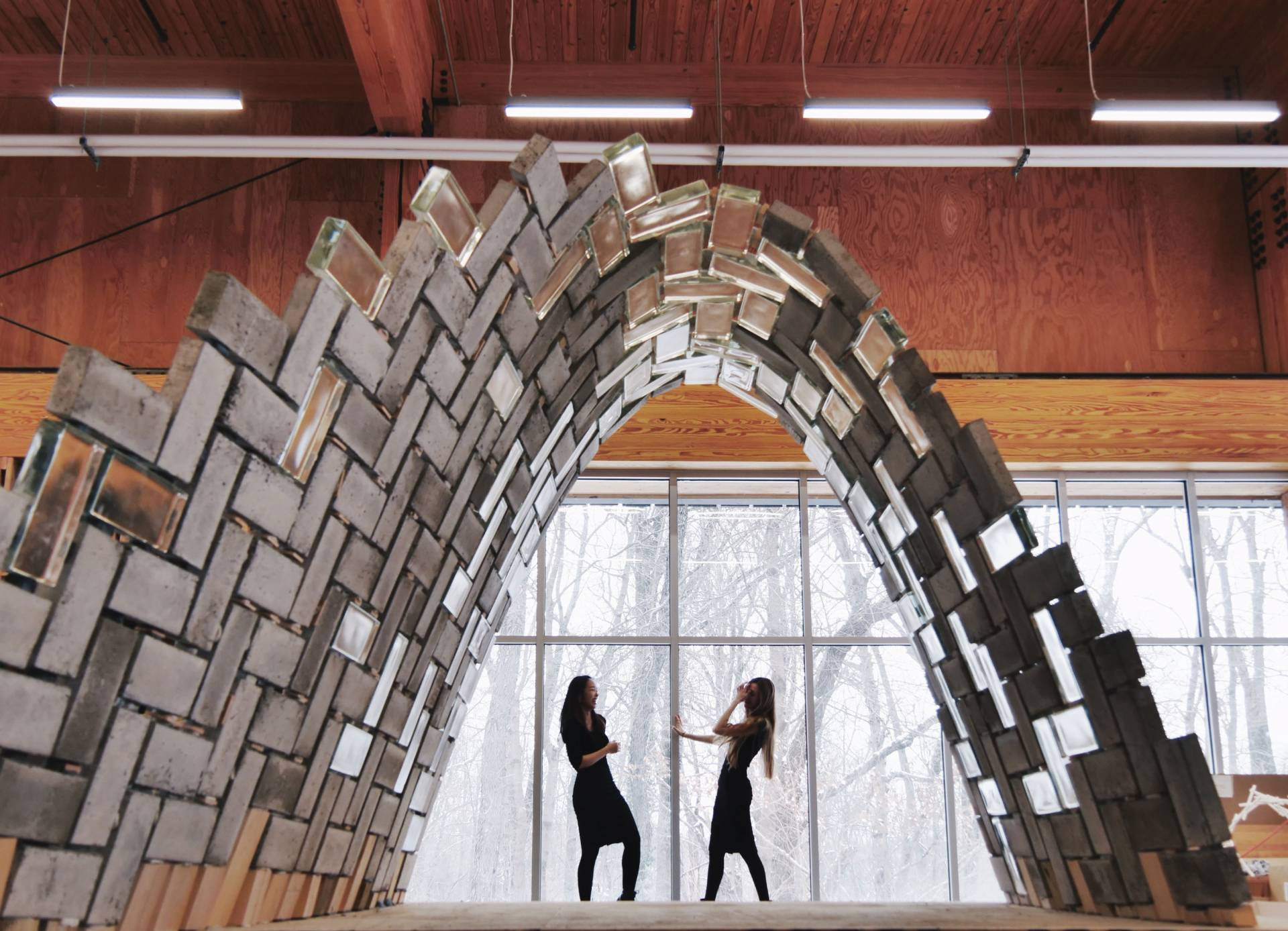 2 archictects stand under a robot-built tunnel