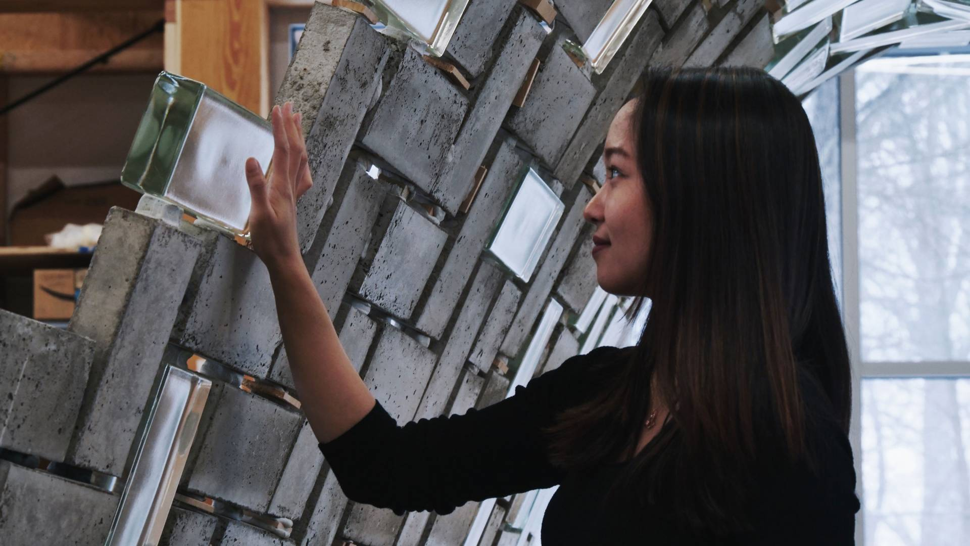 A graduate student touches a glass brick in the structure