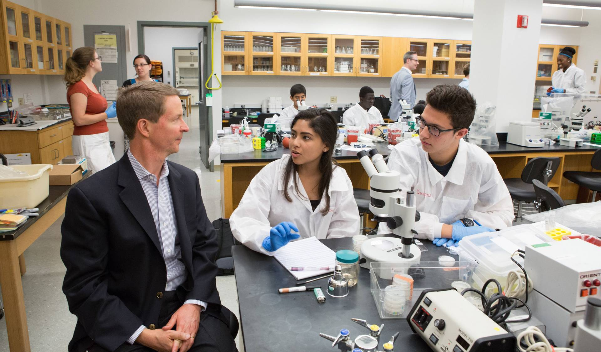 Bob Peck speaks to students while in a laboratory