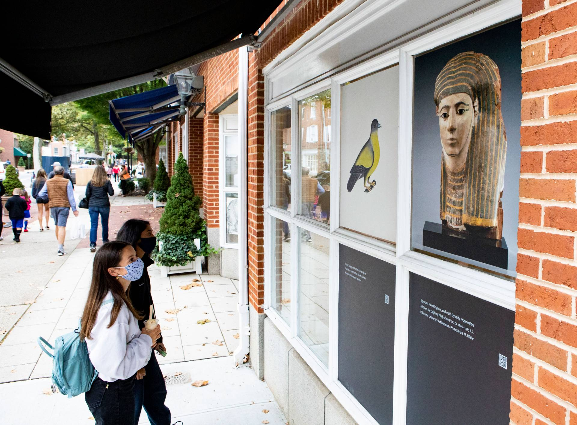 passers-by stop to look at art in shop windows