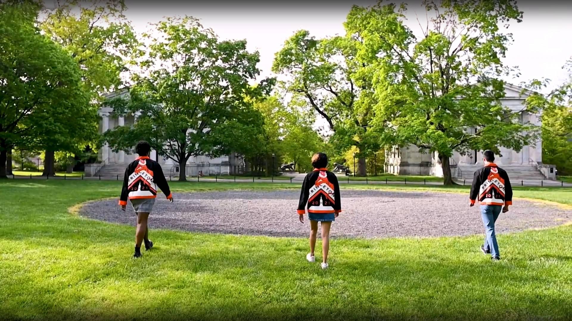 Three students walk toward the cannon