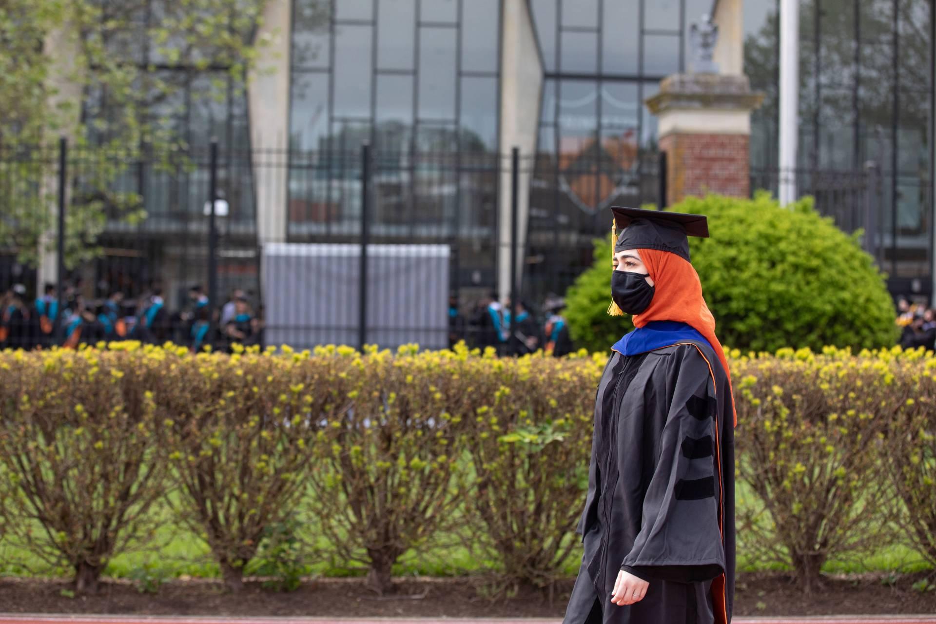 A graduate student walks to the stadium