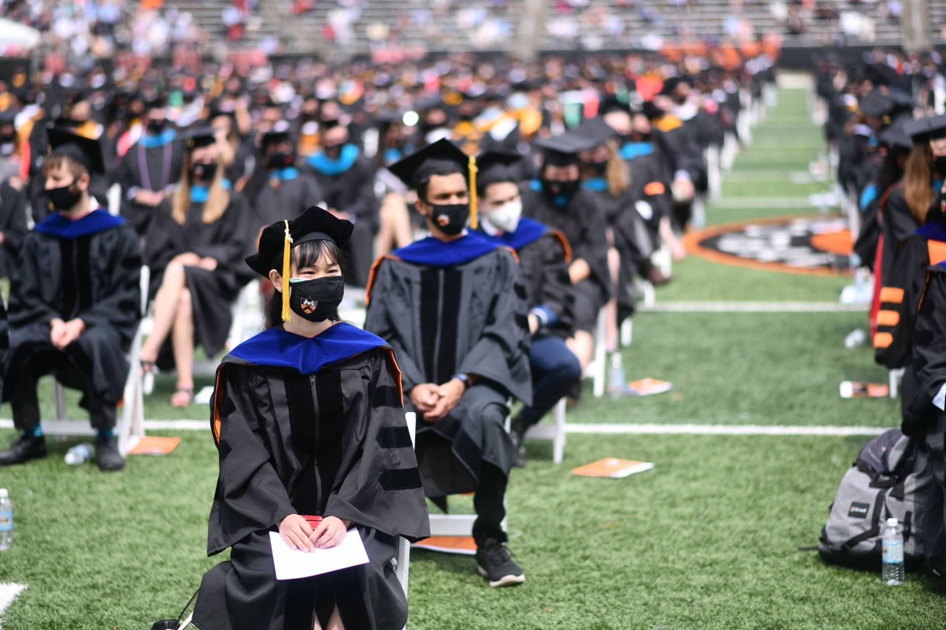 Graduates sit in rows in the stadium