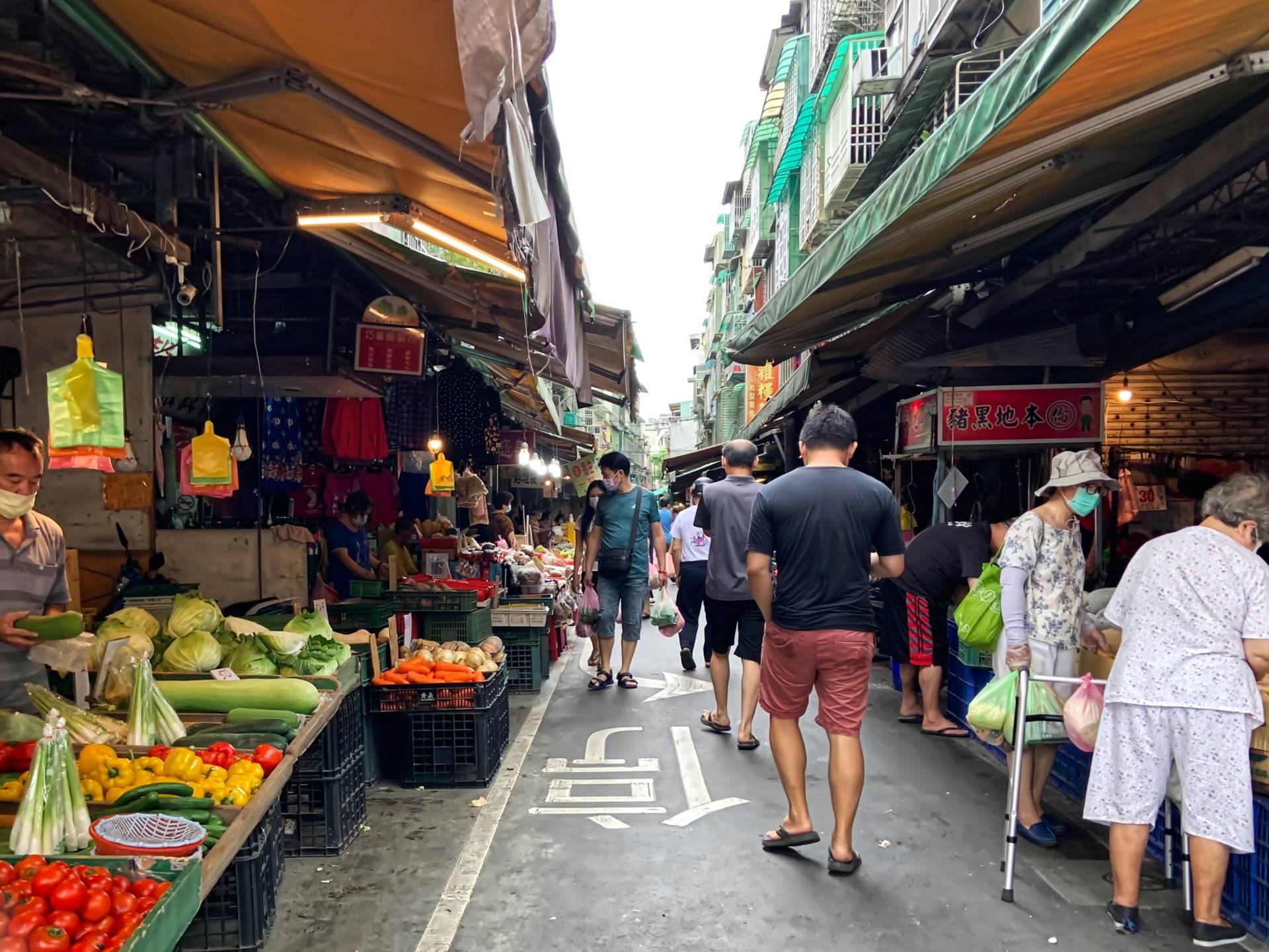 People walk through a wet market in Taiwan