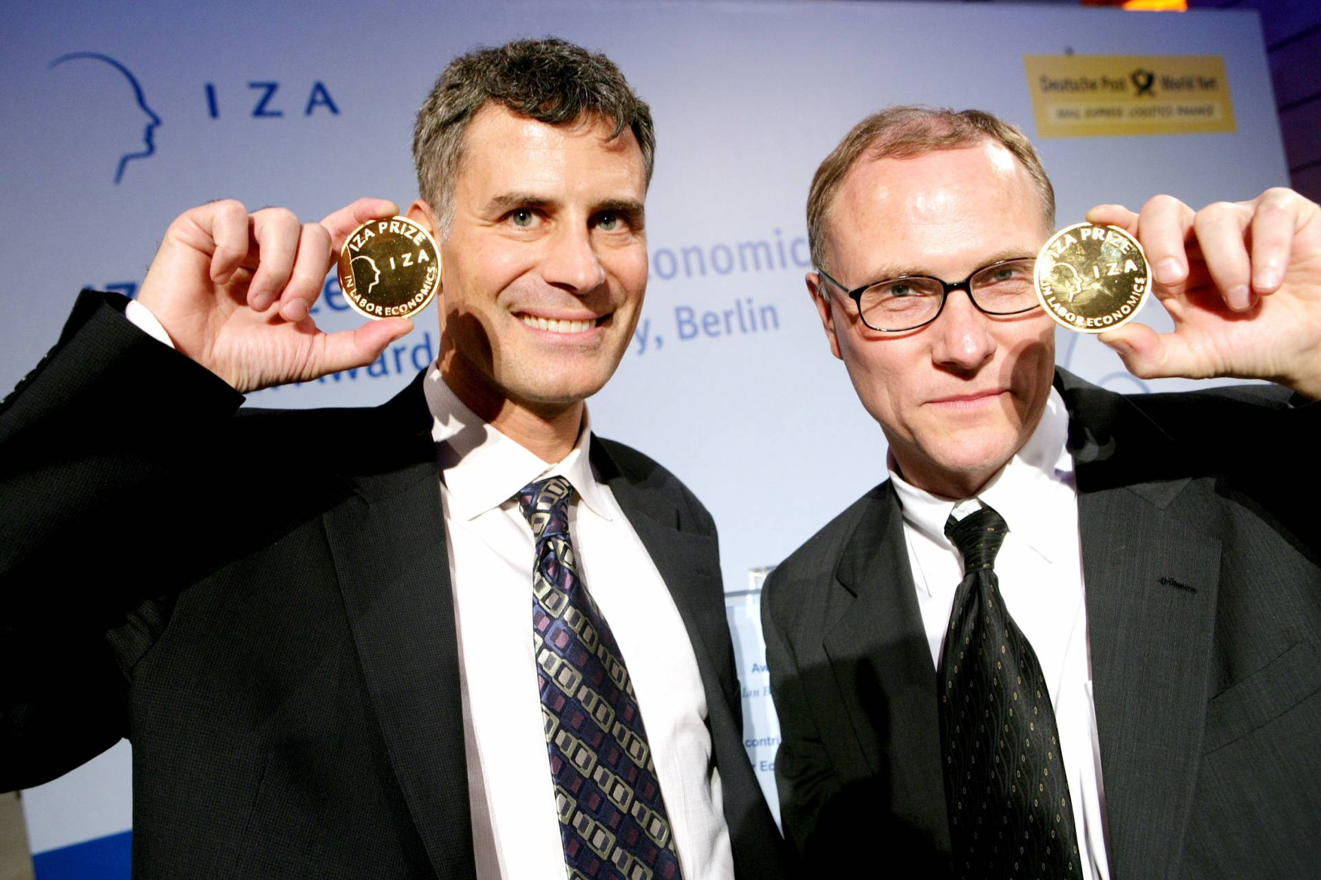 Alan Krueger and David Card hold up their IZA medals