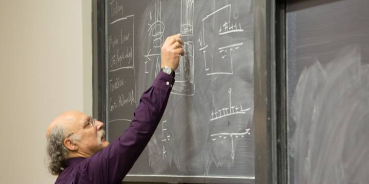 Professor writing on chalk board