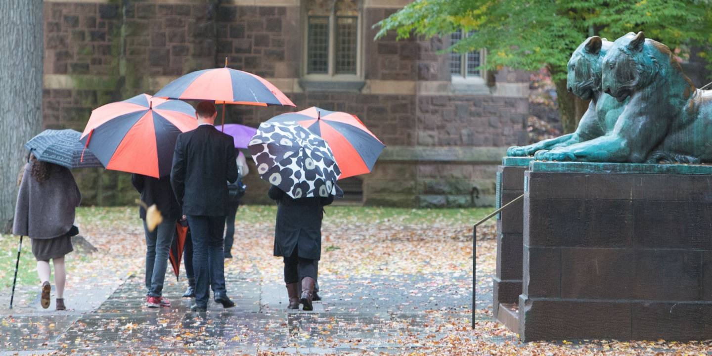 People with umbrellas in front of Nassau Hall
