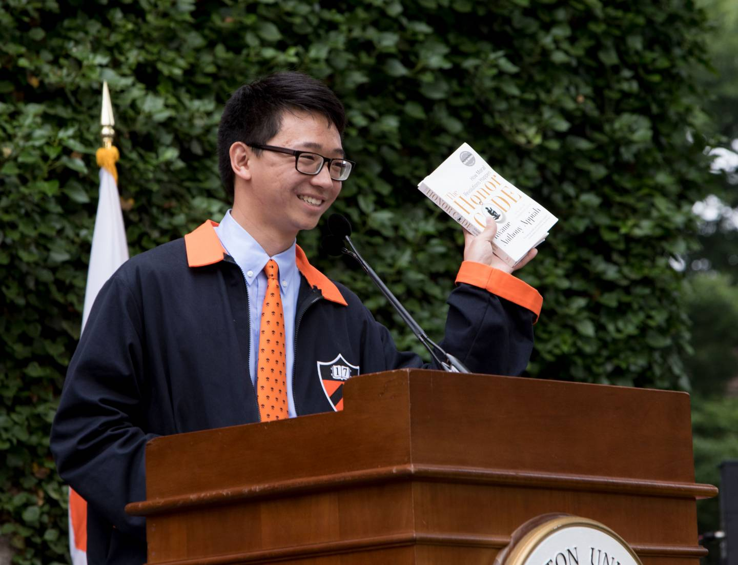 Class president at podium holding book during Class Day 2017 ceremony
