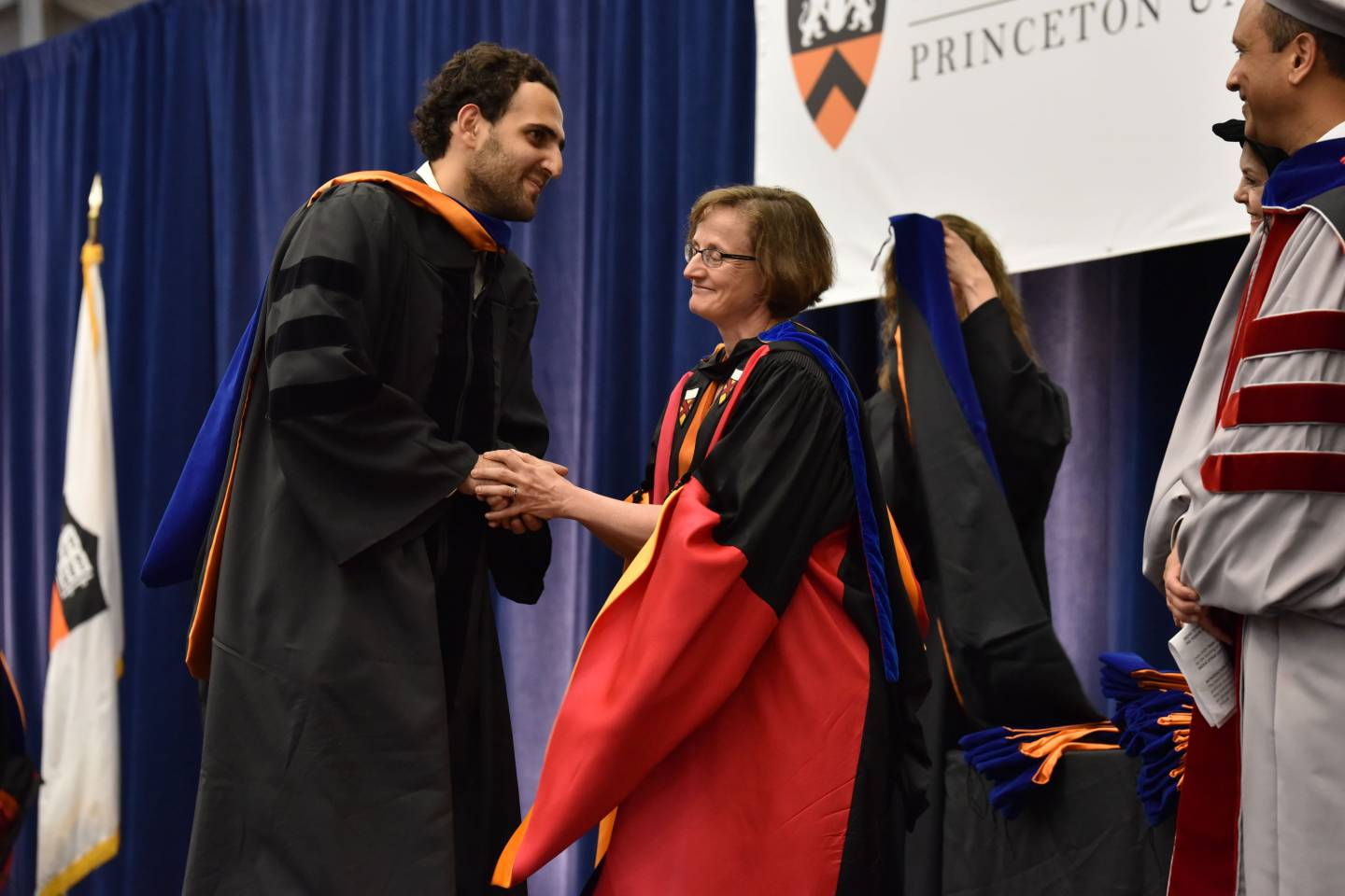 Student shakes hands with advisor at hooding
